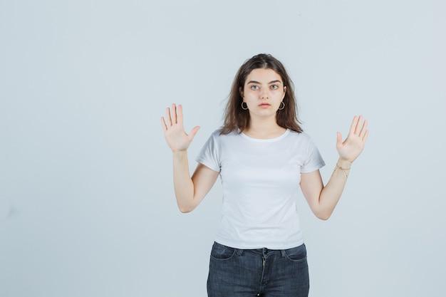 Портрет молодой девушки, поднимающей руки в жесте капитуляции в футболке, джинсах и серьезного вида спереди