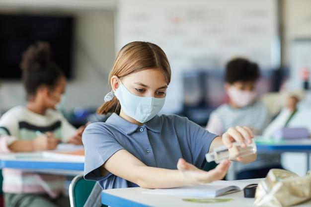 학교 교실에서 손을 소독하는 어린 소녀의 초상화, 코비드 안전 조치, 복사 공간
