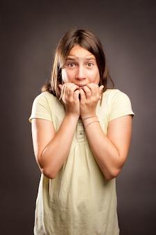 Портрет испуганной девушки на сером
