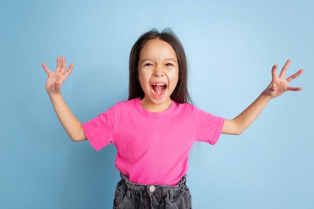 Портрет молодой девушки, кричащей изолированной на синей стене студии