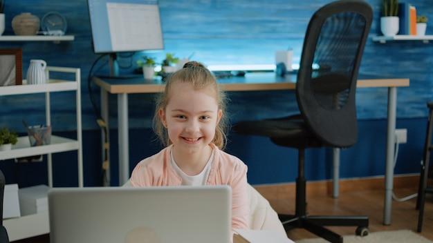 Портрет молодой девушки улыбается и держит ноутбук дома