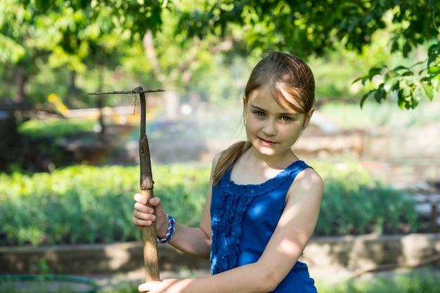 鍬と夏の菜園で屋外に立っている少女の肖像画