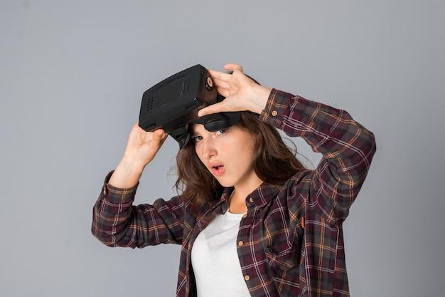 회색 배경 스튜디오에서 가상 현실 안경을 테스트하는 어린 소녀의 초상화