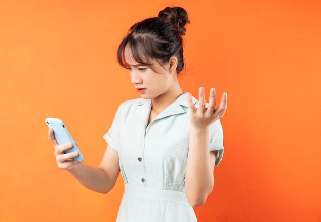 전화를 사용하고 짜증이 나는 어린 소녀의 초상화, 오렌지 배경에 고립