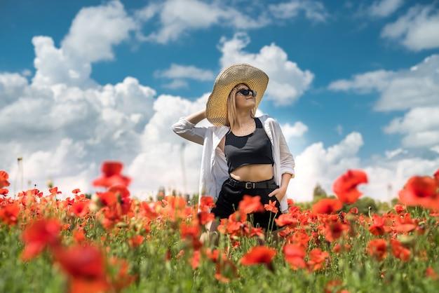 여름 시간에 양 귀 비 분야에서 걷는 젊은 여자의 초상화