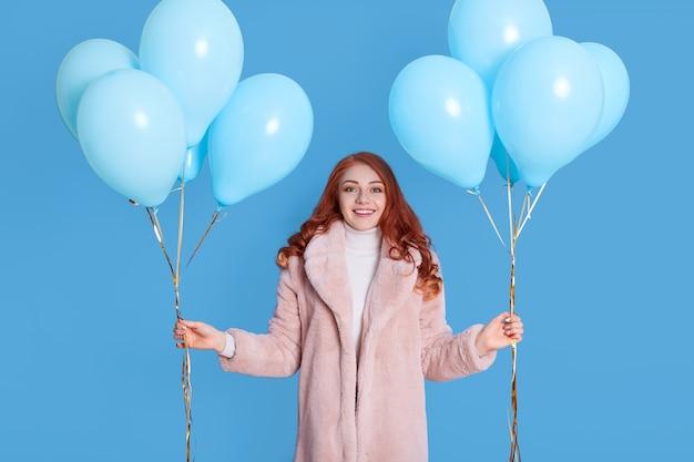 Портрет молодой девушки в бледно-розовой шубе, держащей воздушные шары на день рождения для вечеринки, с рыжими волосами