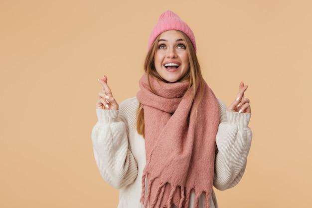 Портрет молодой девушки в зимней шапке и шарфе, улыбающейся и скрещивающей пальцы, изолированной на бежевом