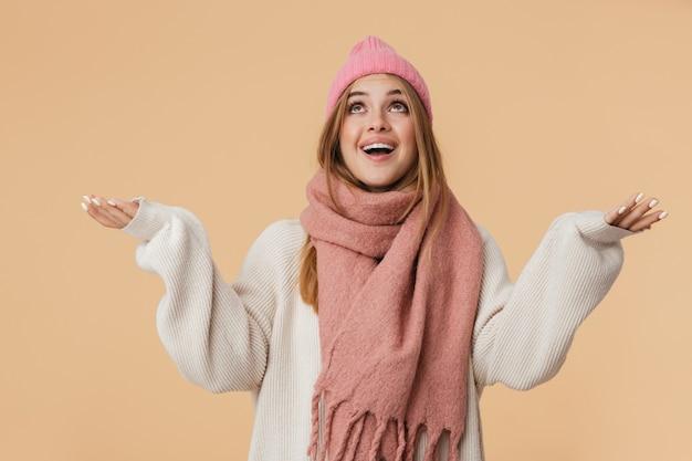 Портрет молодой девушки в зимней шапке и шарфе, улыбающейся и смотрящей вверх с широко раскрытыми руками, изолированными на бежевом