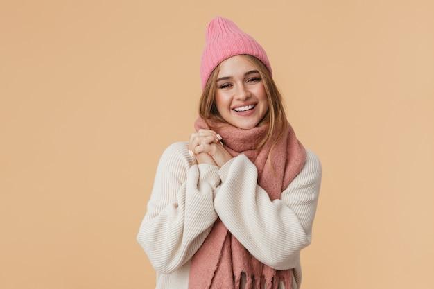 Портрет молодой девушки в зимней шапке и шарфе, улыбающейся и прижимающей руки к груди, изолированной на бежевом
