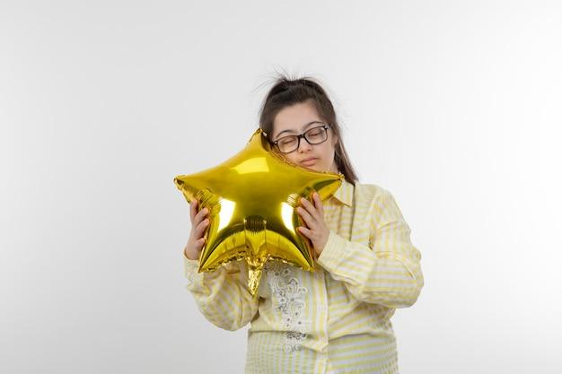 스타의 모양에 공기 풍선을 들고 노란색 체크 무늬 셔츠를 입고 다운 증후군을 가진 젊은 여자의 초상화
