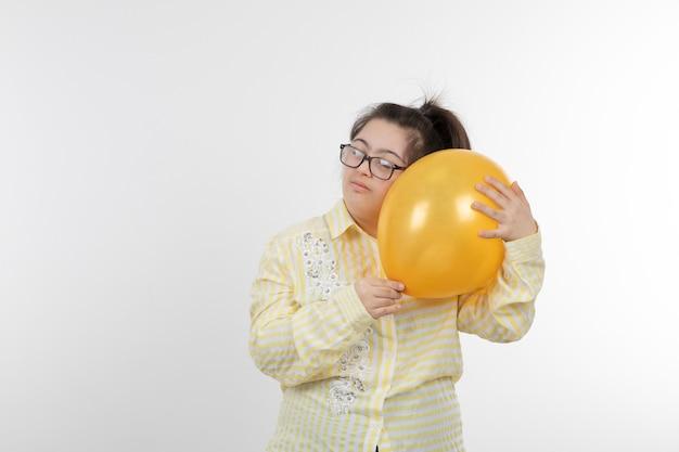 공기 풍선을 들고 노란색 체크 무늬 셔츠를 입고 다운 증후군을 가진 어린 소녀의 초상화