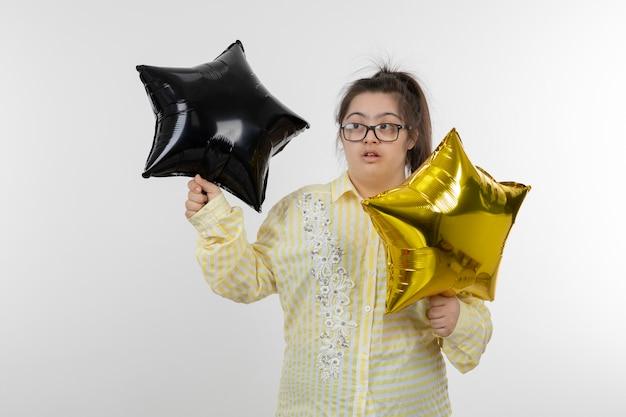 별 모양에 공기 풍선을 들고 노란색 체크 무늬 셔츠를 입고 다운 증후군을 가진 젊은 여자의 초상화.