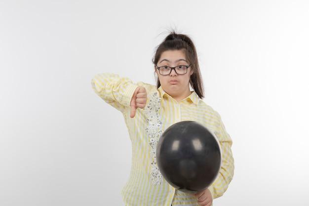 아래로 엄지 손가락을 보여주는 공기 풍선과 함께 노란색 체크 무늬 셔츠를 입고 다운 증후군을 가진 어린 소녀의 초상화