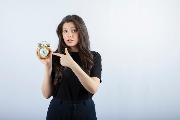 灰色の上に立っている目覚まし時計を持つ少女の肖像画。