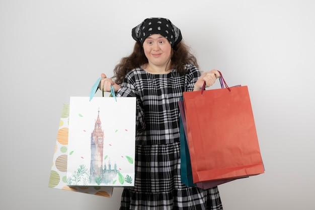 Портрет молодой девушки с синдромом дауна, держащей кучу хозяйственной сумки.