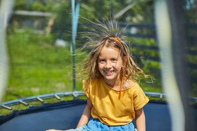 Портрет молодой девушки с наэлектризованными волосами на батуте на открытом воздухе, на заднем дворе дома в солнечный летний день, летние каникулы, счастливый маленький ребенок прыгает на батуте