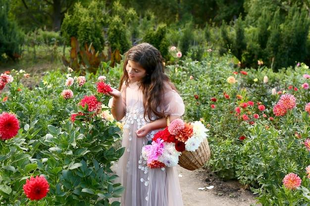 庭の花を持つ少女の肖像画。ダリアの花の中で美しい少女