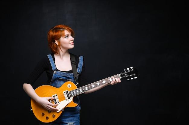黒の背景上のギターを持つ若い女の子の肖像画。