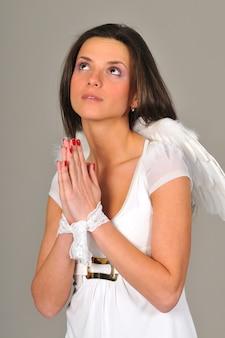 천사 날개, 접힌 손, 눈가리개와 흰 드레스와 젊은 여자의 초상화. 회색 벽에 절연 프리미엄 사진