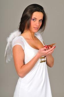 천사 날개와 하얀 드레스를 입고 젊은 여자의 초상화. 컬러 벽에 절연