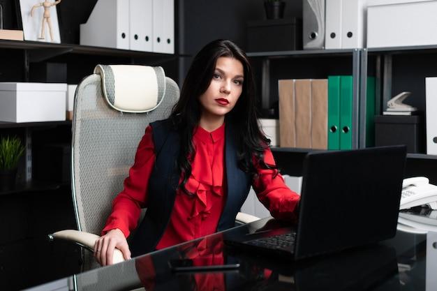 Портрет молодой девушки с ноутбуком в офисе