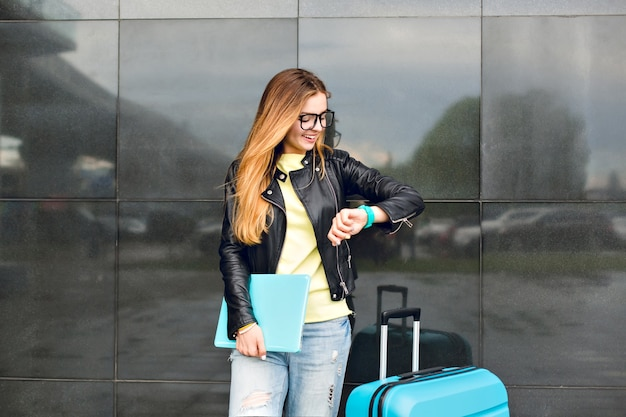 メガネの長い髪の少女の肖像画は、黒の背景に外に立っています。彼女はジーンズと黒のジャケットを着ており、ラップトップを持っています。彼女は時計を見ています。
