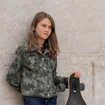 スケートボードを持つ若い女の子の肖像画