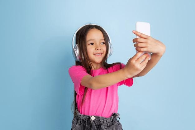 Портрет молодой девушки со смартфоном и наушниками, изолированной на синей стене студии