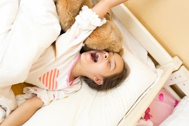 ベッドであくびをして手を伸ばす若い女の子の肖像画
