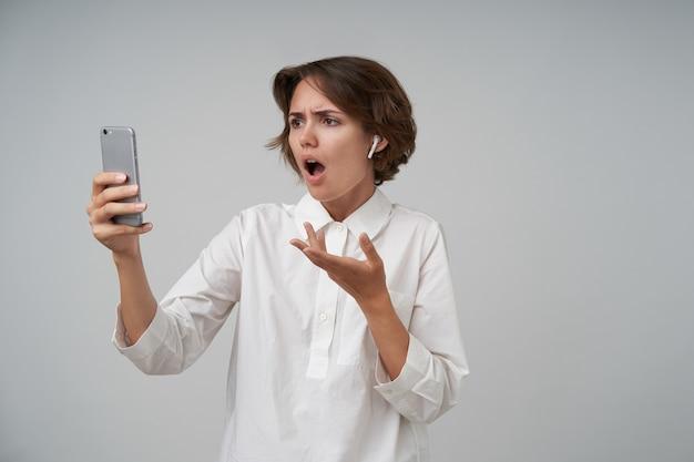 Портрет молодой мрачной женщины с непринужденной прической, держащей мобильный телефон в поднятой руке и имеющей видеозвонок, смотрящей на экран с потрясенным лицом, позирующей в строгой одежде