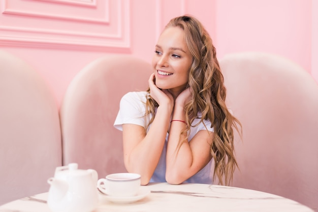 彼女の仕事の休憩中にモダンなカフェでお茶を飲む若いゴージャスな女性の肖像画