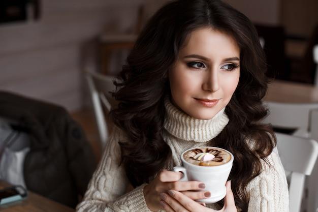 お茶を飲みながら余暇を楽しんで、カフェの窓から考え込むように考えている豪華な若い女性の肖像画