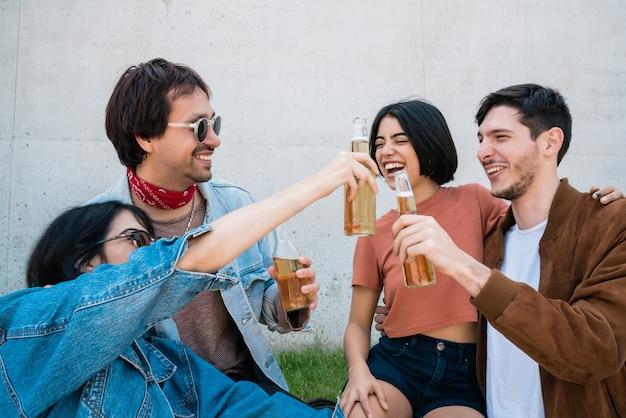 一緒に楽しい時間を過ごし、屋外に座ってビールを飲む友人の若いグループの肖像画。ライフスタイルと友情の概念。