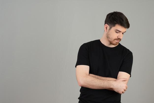 若い男の肖像画。ハンサムな男は灰色で腕を組んだ。