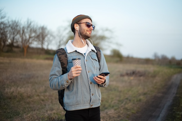 ホットコーヒーと屋外のイヤホンとスマートフォンのカップを保持している若い男の肖像画