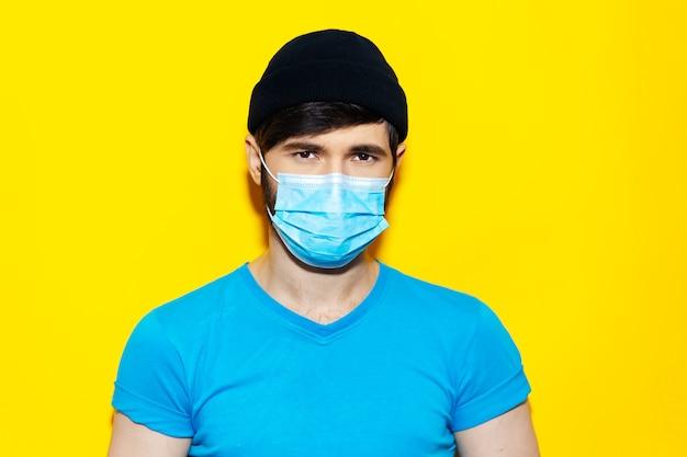 코로나 바이러스에 대한 의료 얼굴 마스크를 쓰고 파란색 셔츠에 젊은 남자의 초상화