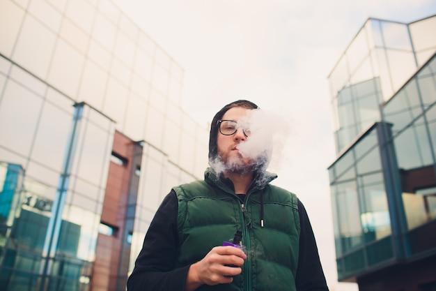 Портрет молодого парня с большой бородой в стеклах vaping электронная сигарета напротив городской предпосылки.