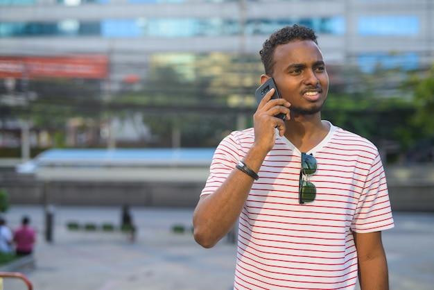 Портрет молодого красивого африканского бородатого мужчины с афро-волосами, исследующего улицы города на открытом воздухе