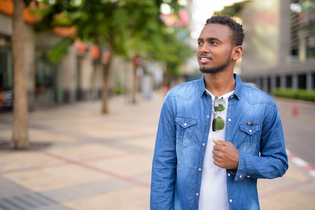 屋外の街の通りを探索するアフロの髪を持つ若いハンサムなアフリカのひげを生やした男の肖像画