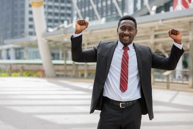 Портрет молодого красивого африканского бизнесмена в костюме с видом на современное здание в городе на открытом воздухе