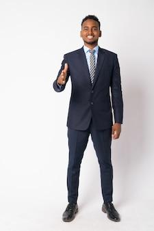Портрет молодого красивого африканского бизнесмена в костюме у белой стены