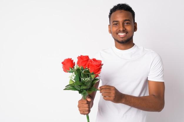 白い壁に対してバレンタインデーの準備ができて若いハンサムなアフリカ人の肖像画