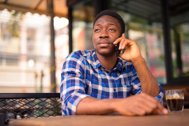 コーヒーショップでリラックスした若いハンサムなアフリカ人の肖像画