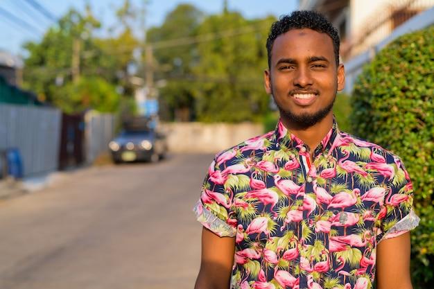 屋外の通りで若いハンサムなアフリカの観光客の男の肖像画