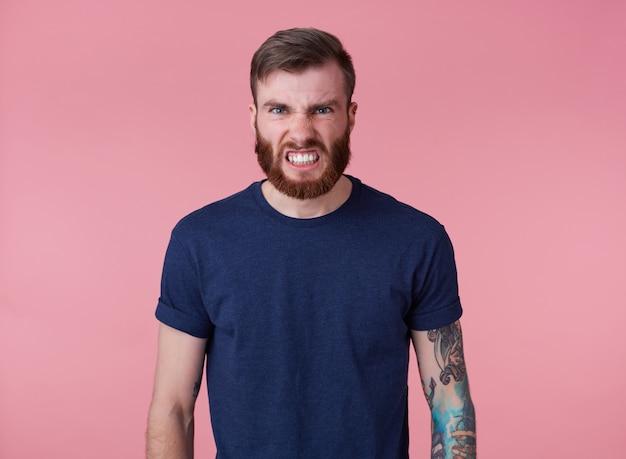 赤いtシャツを着た若いハンサムな怒っている赤いひげを生やした男の肖像画は、ピンクの背景の上に立って、嫌悪感を持ってカメラを見て、彼の歯をむき出しにします。