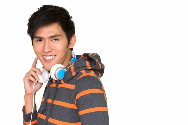 흰 벽에 고립 된 헤드폰으로 웃 고 젊은 잘 생긴 아시아 남자의 초상화
