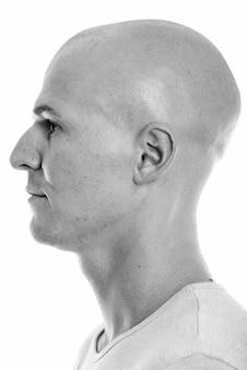 Портрет молодого красивого лысого мужчины, изолированного на белом в черно-белом