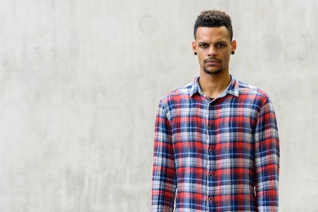 屋外のコンクリートの壁に対して若いハンサムなひげを生やしたアフリカの流行に敏感な男の肖像画