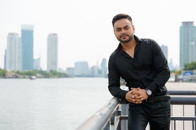 Портрет молодого красивого бородатого индийского бизнесмена в городе на открытом воздухе
