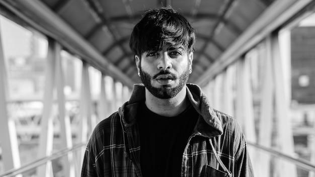 黒と白で屋外の街の歩道橋で若いハンサムなひげを生やしたインドの流行に敏感な男の肖像画